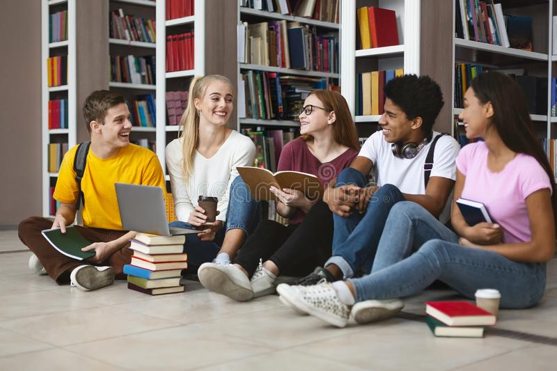 Classmates sitting on floor at library, chatting while studying. Multiracial classmates sitting on floor at library in campus and studying, preparing for exams stock image