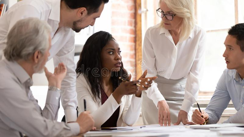 Multiracial colleagues brainstorming discussing ideas at meeting. Multiracial motivated company employees discuss business project at briefing in office, diverse stock images