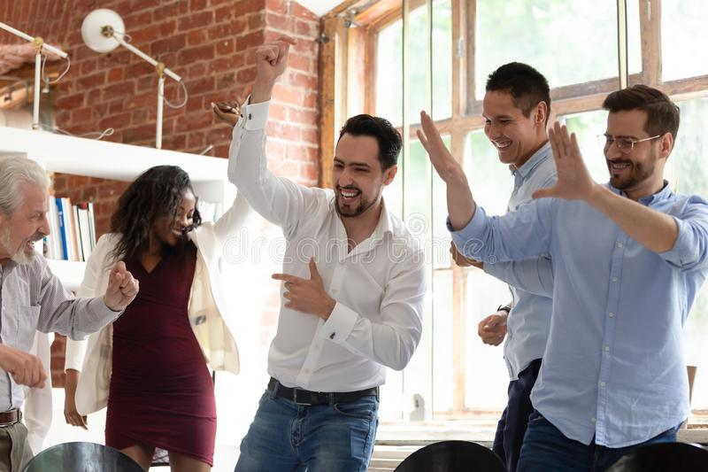 Multiracial colleagues dancing enjoy corporate party or celebrating successful deal stock images