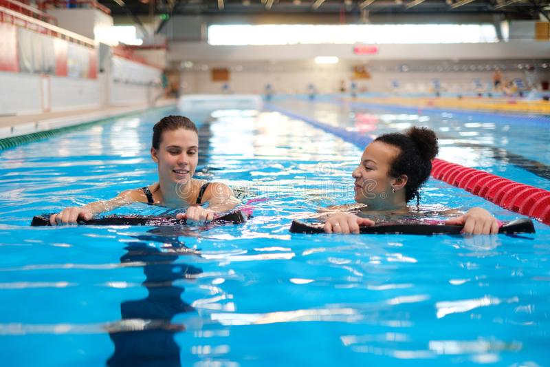 Multiracial couple attending water aerobics class in a swimming pool.  royalty free stock images
