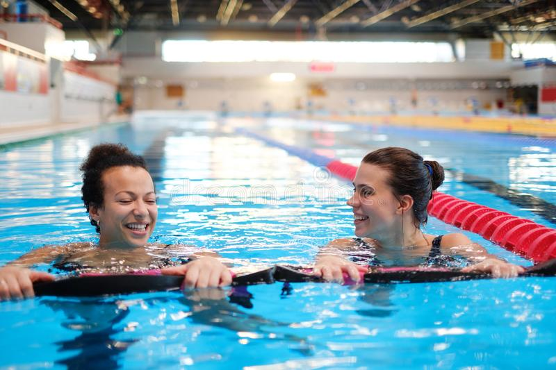 Multiracial couple attending water aerobics class in a swimming pool.  royalty free stock photos