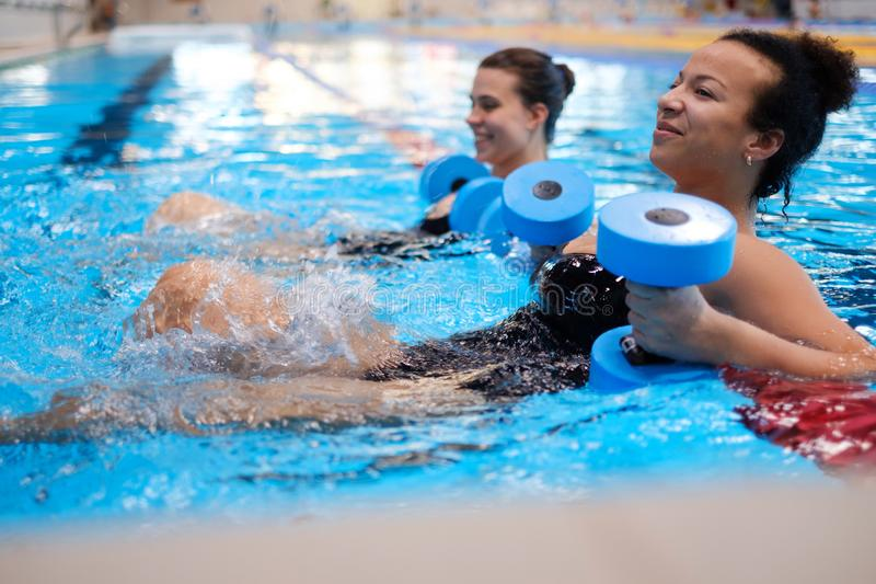 Multiracial couple attending water aerobics class in a swimming pool.  royalty free stock image