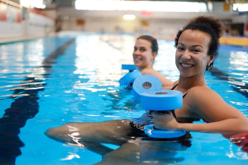 Multiracial couple attending water aerobics class in a swimming pool.  stock photo