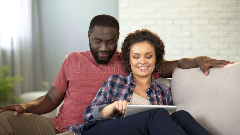 Multiracial couple booking tickets and hotel on tablet, planning vacation online stock photos