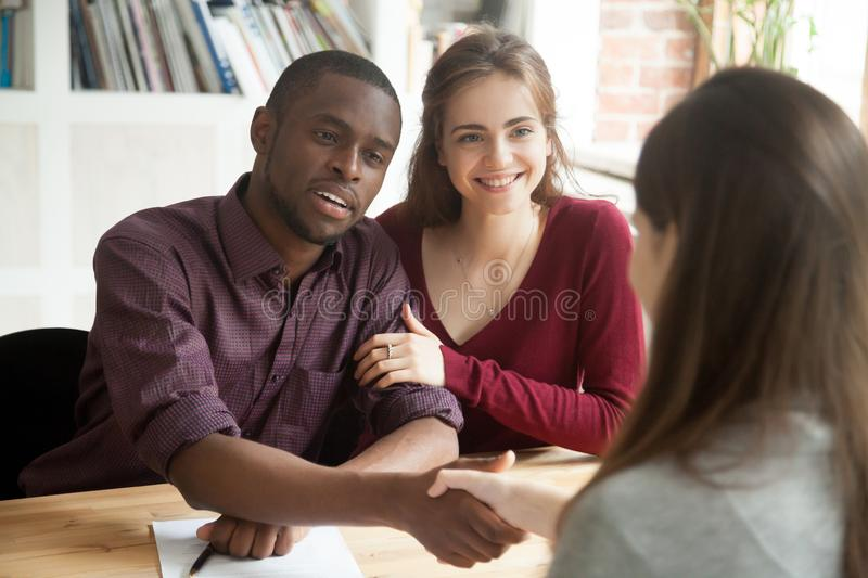 Multiracial couple excited with successful house purchase deal stock image