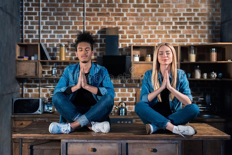 multiracial couple with eyes closed sitting in lotus position in kitchen royalty free stock image
