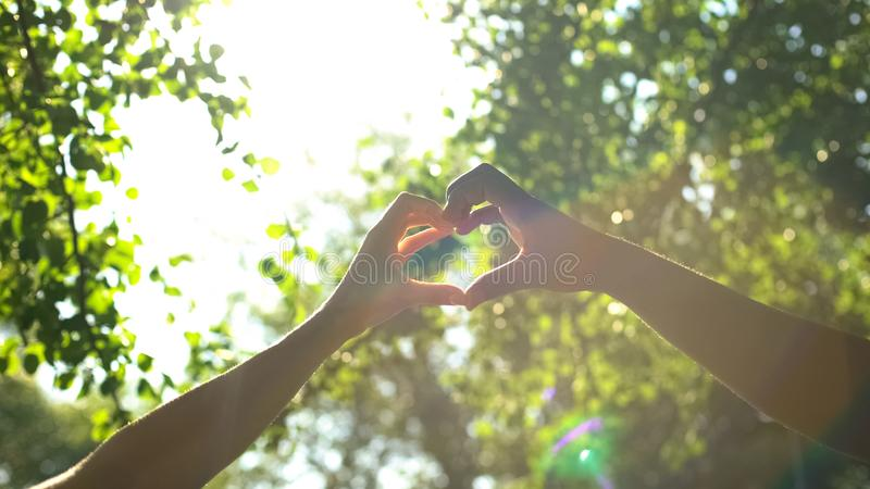 Multiracial couple hands in heart shape, interracial friendship, love and care. Stock photo royalty free stock photo