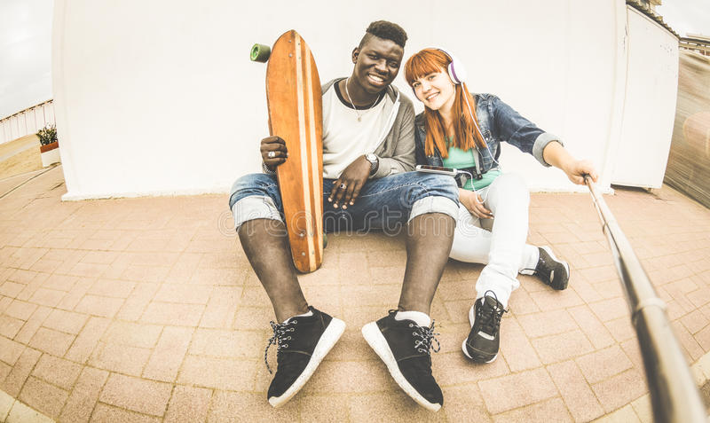 Multiracial couple in love taking selfie having fun together royalty free stock photography