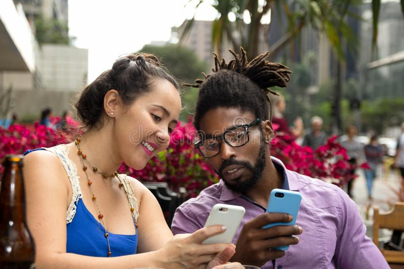 Multiracial couple at outdoor table in restaurant or bar drinking and using cell phone royalty free stock image
