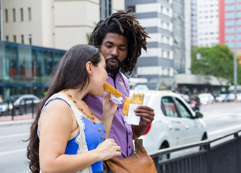 Multiracial couple sharing in the streets brazilian food known as Pastel - asian recipe stock photos