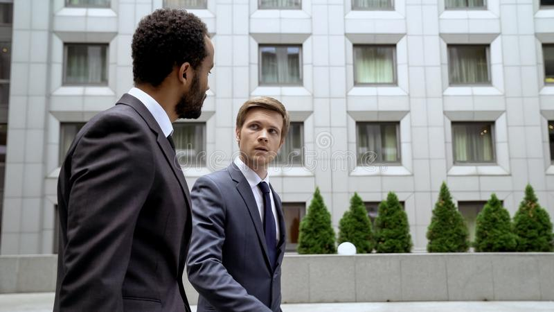 Multiracial coworkers walking near business center, discussing issues at break. Stock photo stock photography