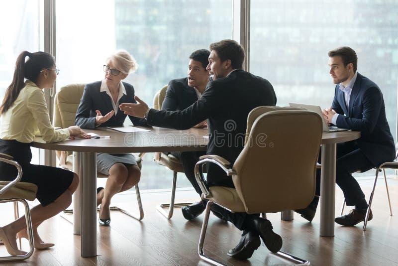 Multiracial drużyny grupowy kwestionować w biurowej sala posiedzeń przy spotkaniem zdjęcia stock