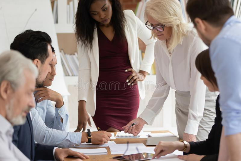 Multiracial employees brainstorm discussing ideas at briefing. Focused middle-aged businesswoman talk head company team meeting in office, concentrated royalty free stock photography