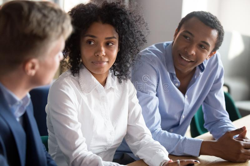 Multiracial employees brainstorm negotiating at office meeting. Multiracial employees sit at office desk brainstorming discussing project at business meeting stock photos
