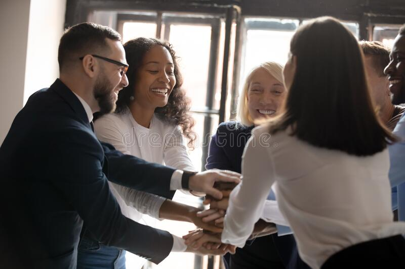 Multiracial entrepreneurs stacked hands together celebrating common victory royalty free stock photo