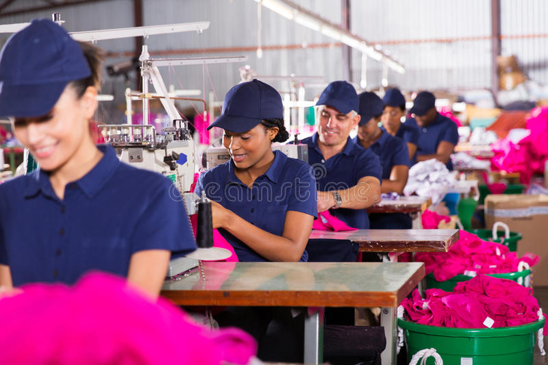 Multiracial factory workers. Group multiracial factory workers sewing in clothing factory stock photography