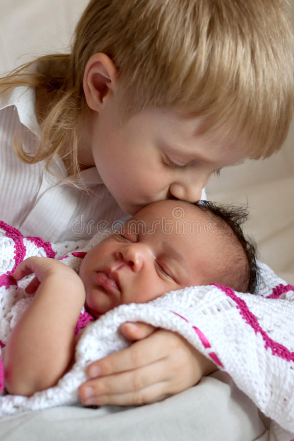 Multiracial family concept. Brother kissing newborn stock photo