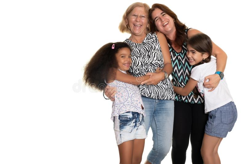 Multiracial family hugging, Grandmother, mom and her two mixed race daughters stock images