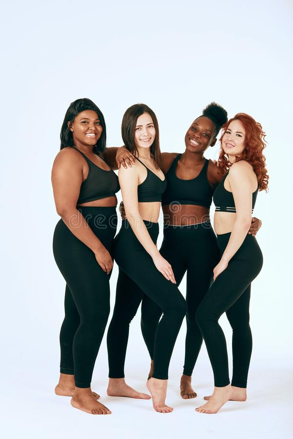 Multiracial females with different size and ethnicity stand together and smile. royalty free stock image