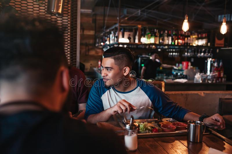 Multiracial friends eat breakfast in lounge bar. Young men chat while having tasty food and drinks. stock images