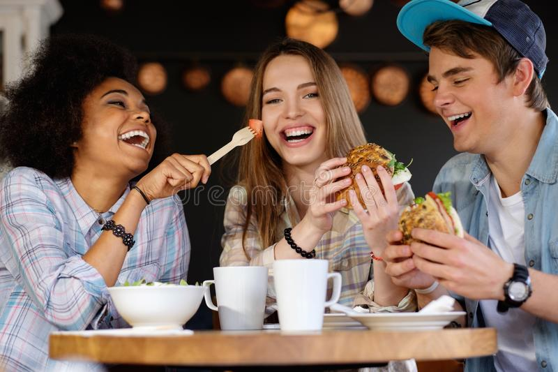 Multiracial friends eating in a cafe. Cheerful multiracial friends eating in a cafe royalty free stock image