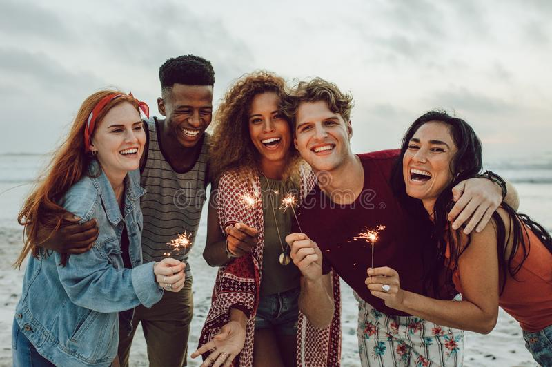 Multiracial friends enjoying at beach with sparklers. Group of young men and women having fun with fireworks at the sea shore royalty free stock photo