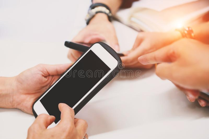 Multiracial friends hand using mobile addicted phone. Wifi connection people on meeting table. Teamwork concept with black blank stock images
