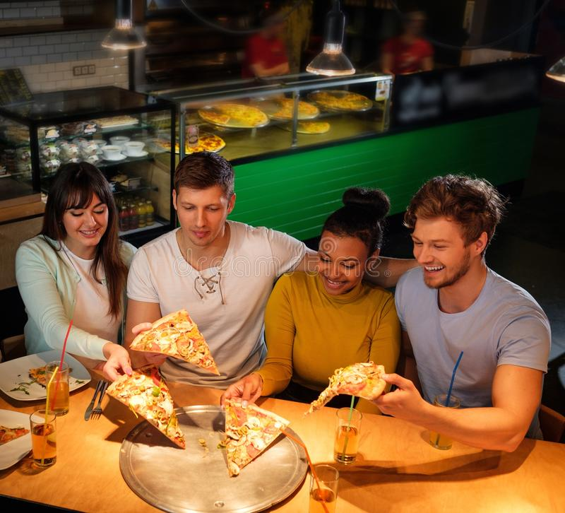 Multiracial friends having fun eating in pizzeria. royalty free stock images