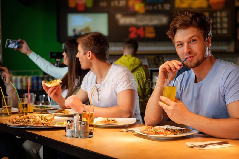 Multiracial friends having fun eating in pizzeria. royalty free stock photography