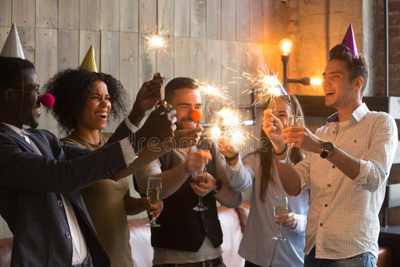 Multiracial friends holding sparklers glasses, celebrating toget royalty free stock photography