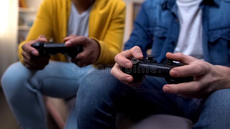 Multiracial friends playing computer games, closeup on hands with joysticks. Stock photo stock images