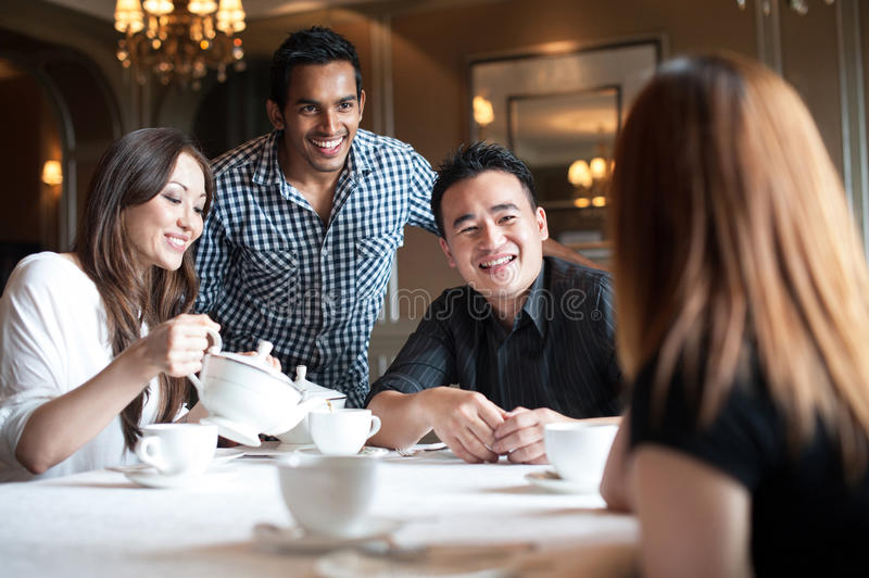Multiracial friends in restaurant smiling royalty free stock images