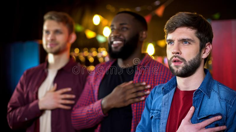 Multiracial friends singing national anthem before football game beginning, pub. Stock photo royalty free stock images