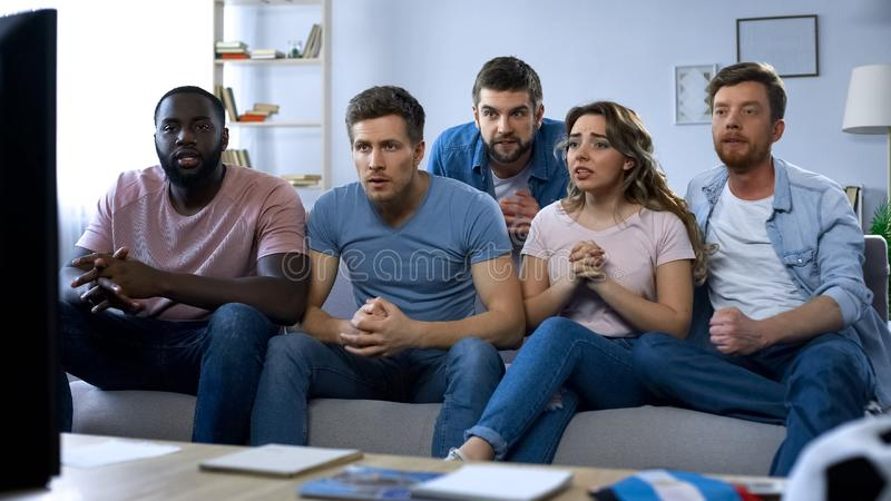 Multiracial friends sitting on couch and comfortably watching sports game on tv. Stock photo royalty free stock image