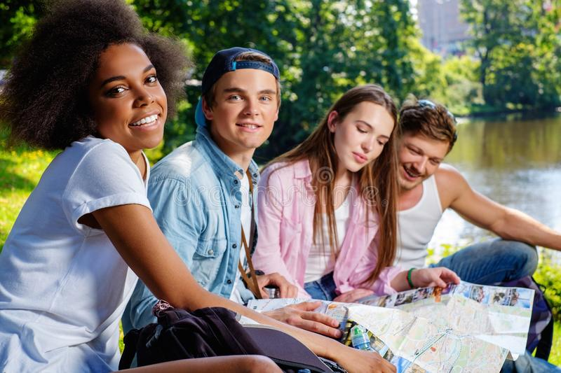 Multiracial friends tourists in a park royalty free stock photography
