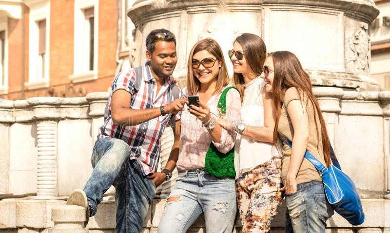 Multiracial friends using mobile smart phone at city tour - Happy friendship concept with student having fun together - Millenial royalty free stock image