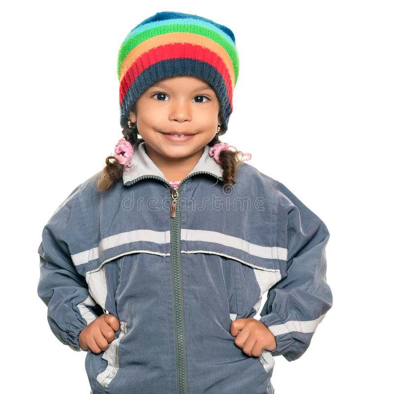 Multiracial girl wearing a jacket and a beanie hat. Multiracial small girl wearing a jacket and a colorful beanie hat isolated on white stock photos