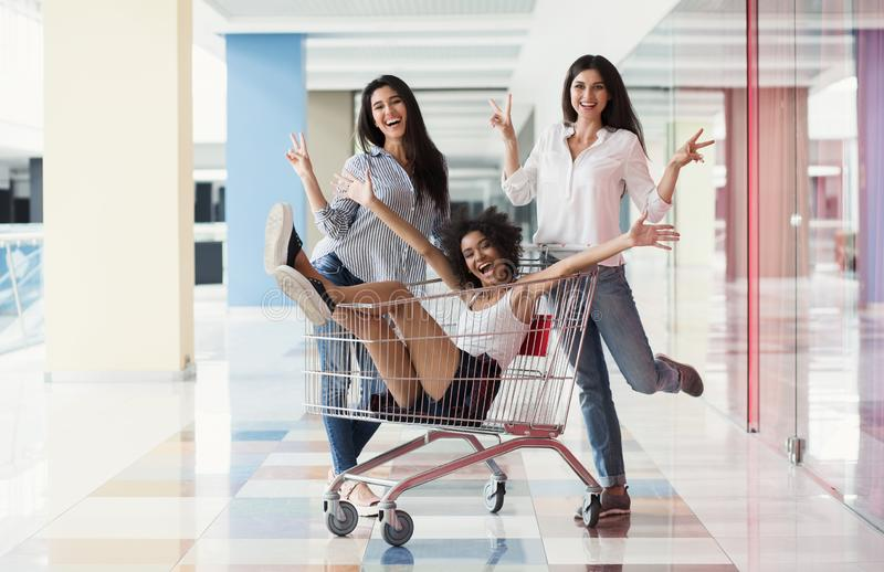 Multiracial girls having fun with supermarket trolley stock photography