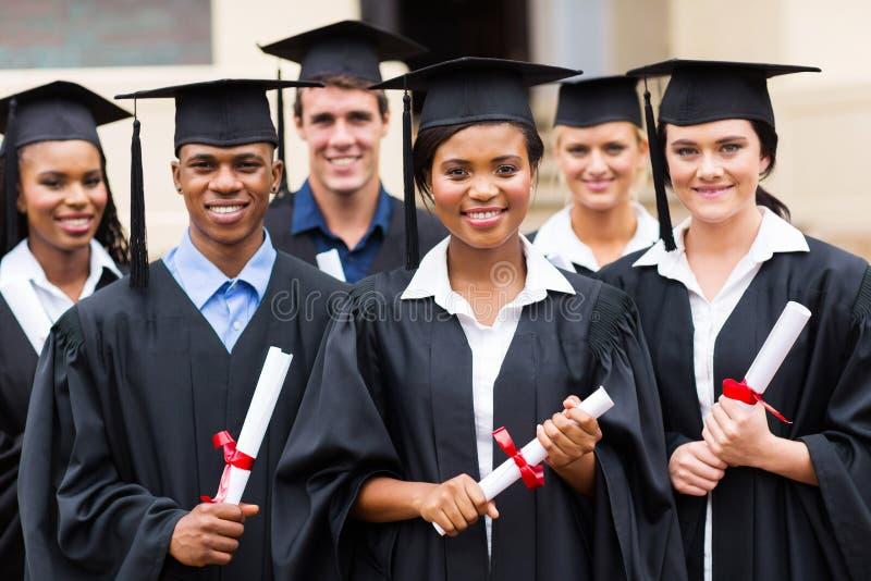 Multiracial graduates. Portrait of multiracial graduates holding diploma stock image
