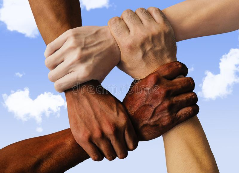 Multiracial group with black african American Caucasian and Asian hands holding each other wrist in tolerance unity love and anti. Racism concept on blue sky stock photo