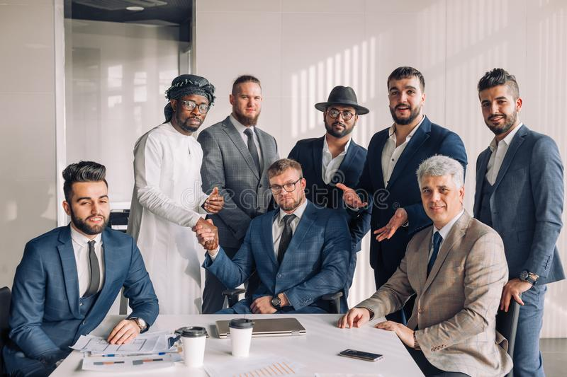 Multiracial group of business team consisting of men only with Executive indoor. Confident multiethnic group of male business partners looking at camera while royalty free stock photos