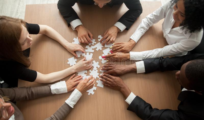 Multiracial group of colleagues engaging in assembling puzzle, t royalty free stock image