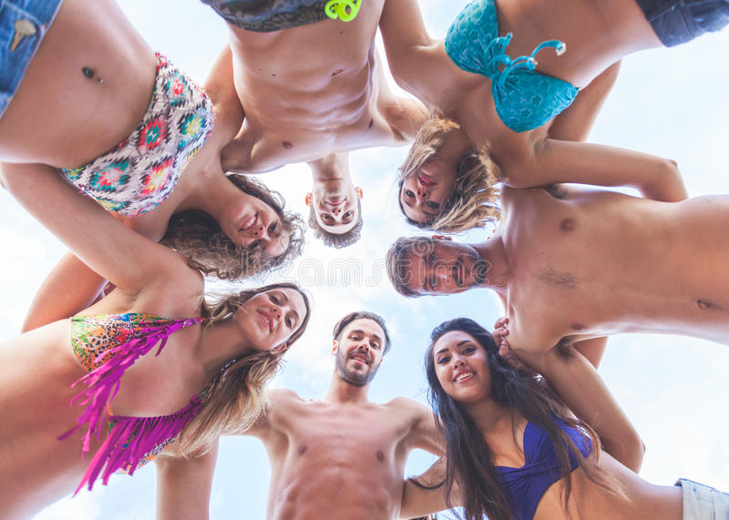Multiracial group of friends embraced at seaside, bottom view. There are four girls and three boys, all of them are wearing swimsuits royalty free stock photo