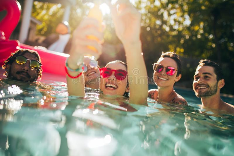 Multiracial group of friends having fun in a pool royalty free stock image