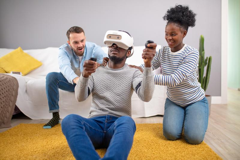 Multiracial group of friends having fun trying on 3D virtual reality goggles. stock photo