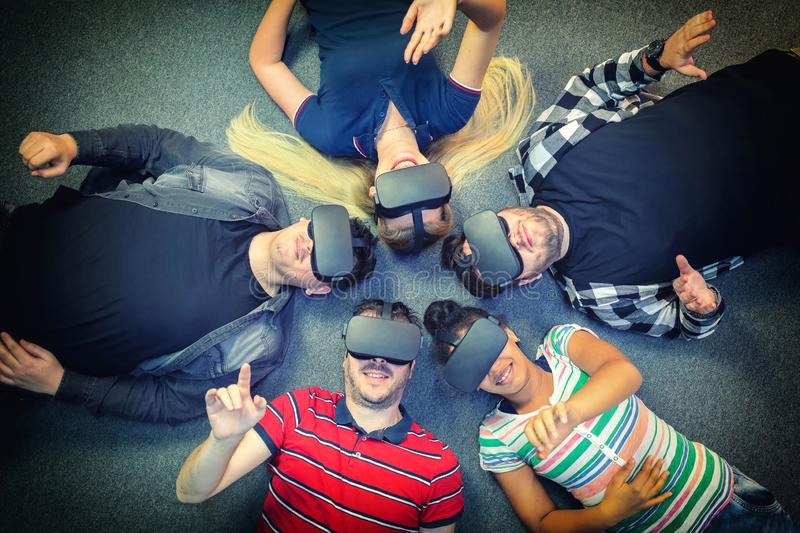 Multiracial group of friends playing on vr glasses indoor - Virtual reality concept with young people having fun together stock photography