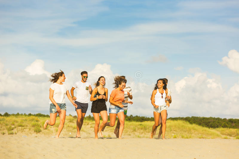 Multiracial group of friends running on the beach royalty free stock photography