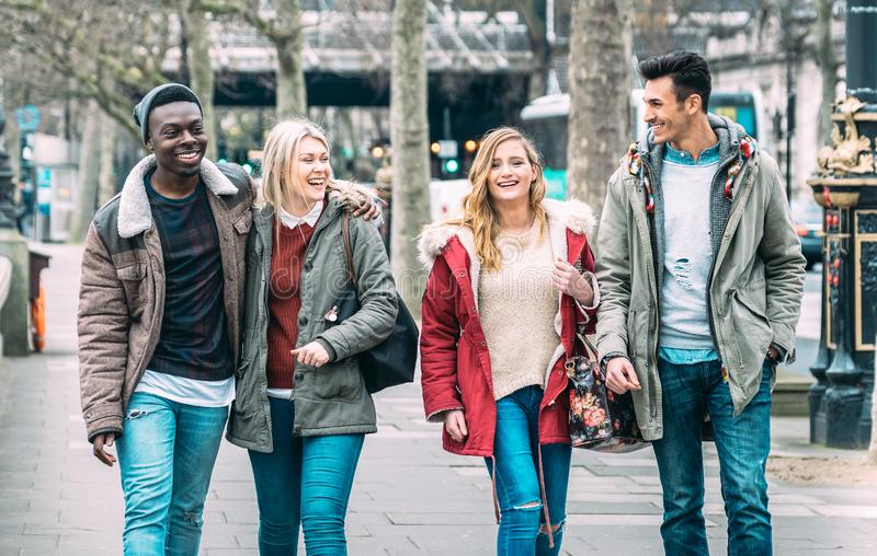 Multiracial group of millenial friends walking at London city center - Next generation friendship concept on multicultural young stock image
