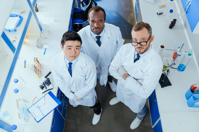 Multiracial group of scientists standing together in chemical lab royalty free stock image