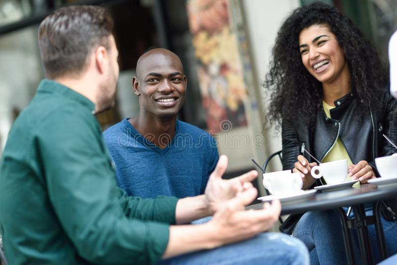 Multiracial group of three friends having a coffee together. stock photo